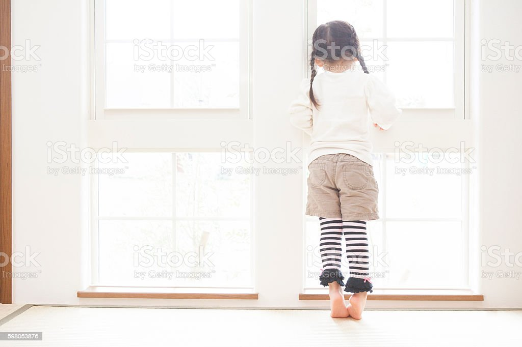Young Japanese girl looking out of a window stock photo