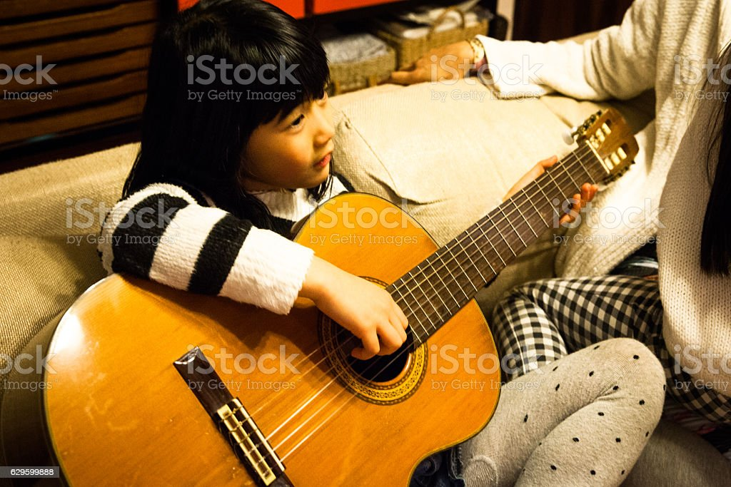 Young Japanese girl playing a classic guitar stock photo