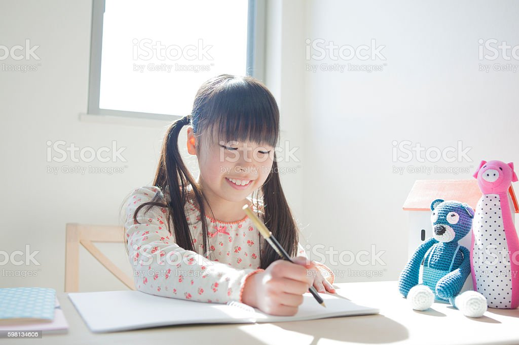 Young Japanese girl sitting at a desk stock photo
