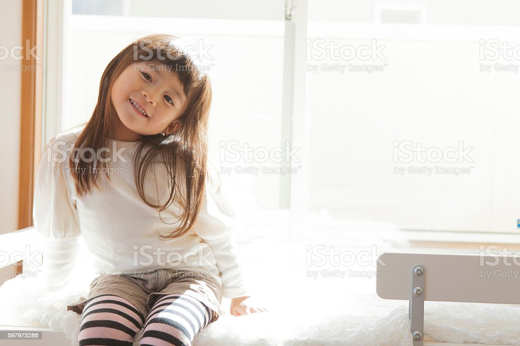 Young Japanese girl sitting in sunlight on a bed stock photo