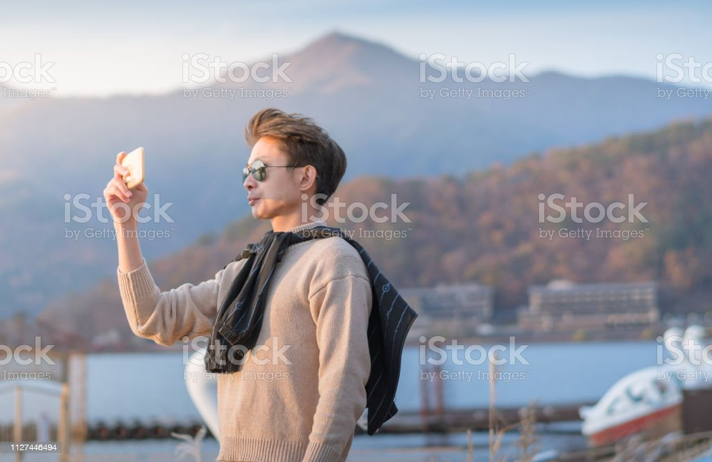 Young japanese guy and asian friend looking for travel location and...