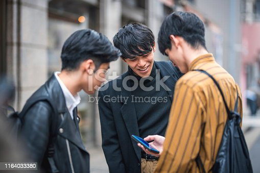 Fashionable Japanese male friends out and about in urban Tokyo pausing to check a smart phone and reply to text messages.