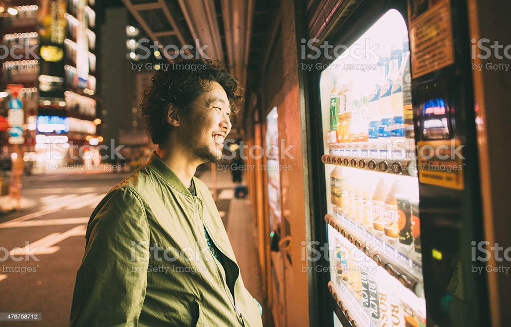 Young japanese man buys drink from the machine stock photo