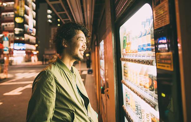 Jungen japanischen Mann kauft Getränk aus der Kaffeemaschine – Foto