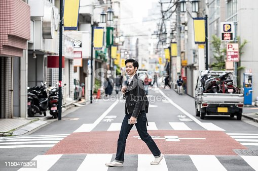 Cool young man in his 20s walking on road in city, smiling, confidence, individuality