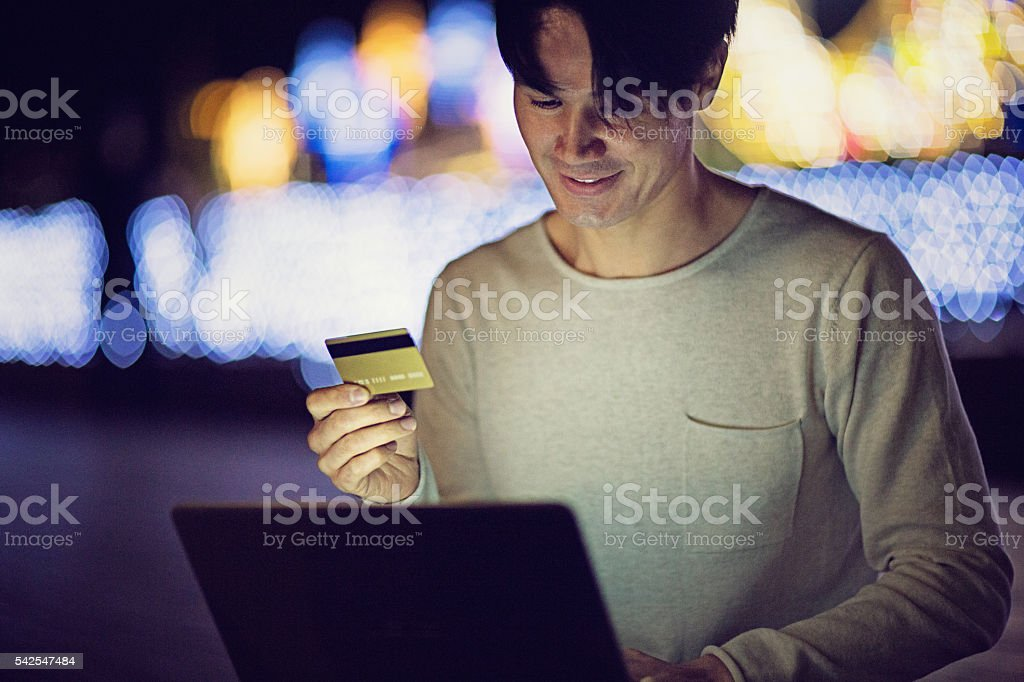 Young Japanese man is  shopping online stock photo