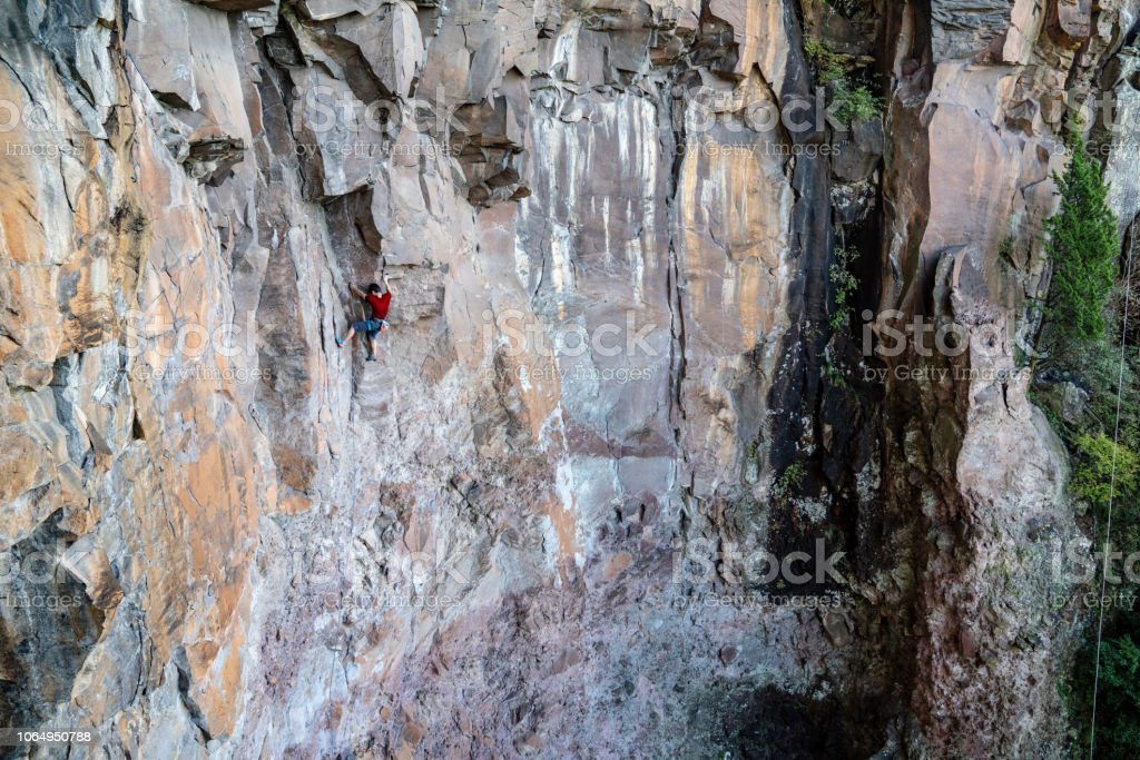 Young Japanese man rock climbing in an extreme location op a huge...