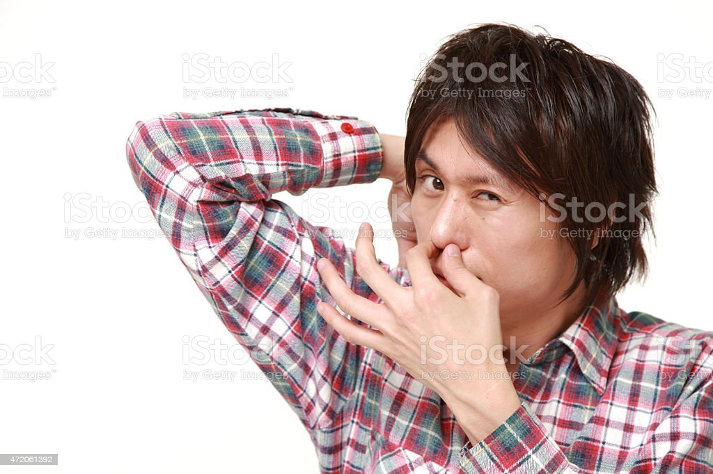 young Japanese man sniffing his armpit stock photo