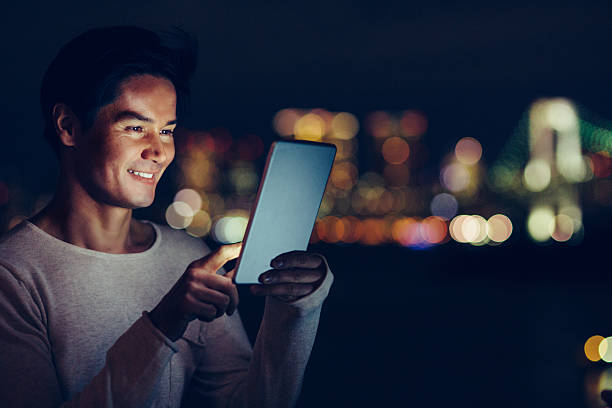 jungen japanischen mann sms auf dem tablette - japanische lampen stock-fotos und bilder