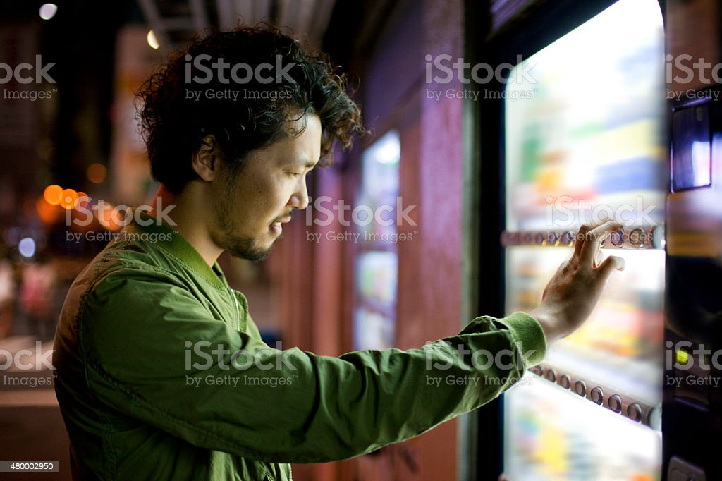 Young Japanese Man Using Vending Mashine in Tokyo. stock photo