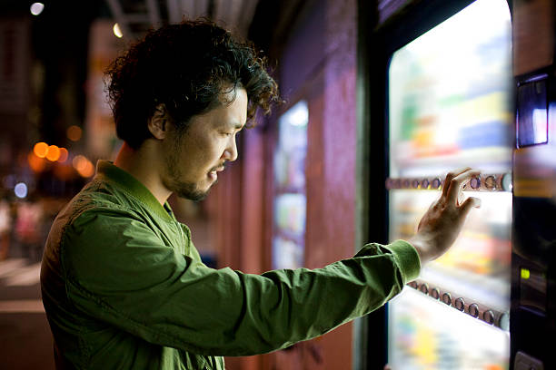 Jungen japanischen Mann mit Verkaufsautomaten Mashine in Tokio. – Foto