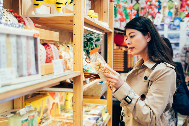 young japanese mom choosing snack for kids - souvenir foto e immagini stock