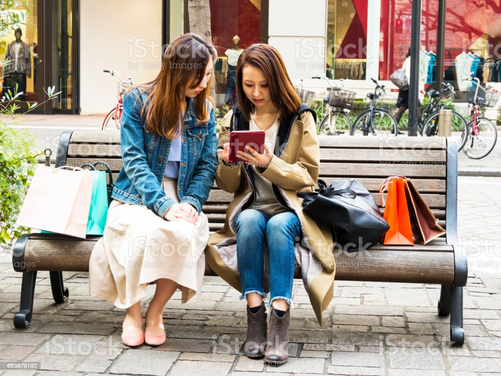 Young Japanese two women talking and checking the tablet. stock photo