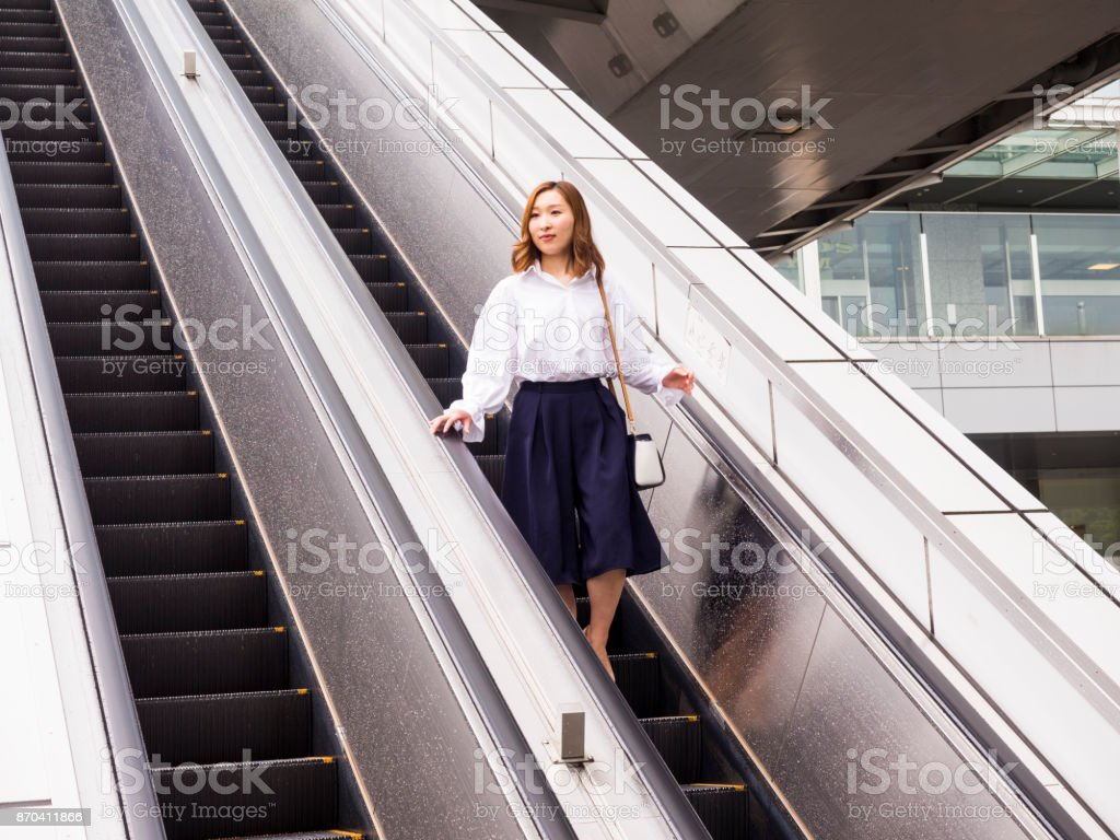 A young Japanese woman comes down from the escalator in the business area. stock photo