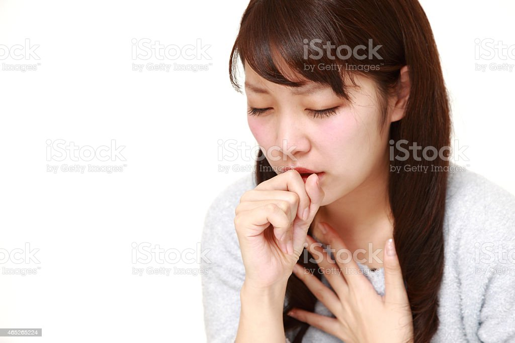 Young Japanese woman coughing and covering her mouth stock photo