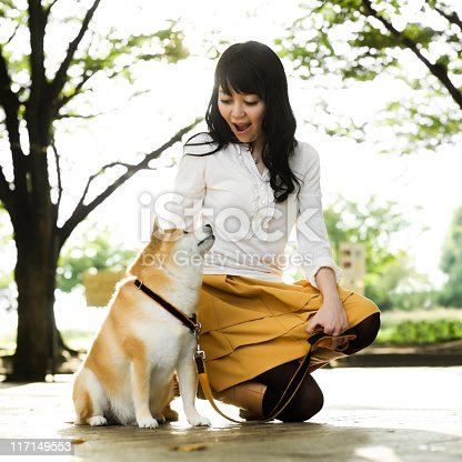 istock Young Japanese Woman Crouching to Pet a Dog 117149553