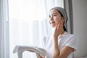 部屋でスキンケアをしている日本の若い女性