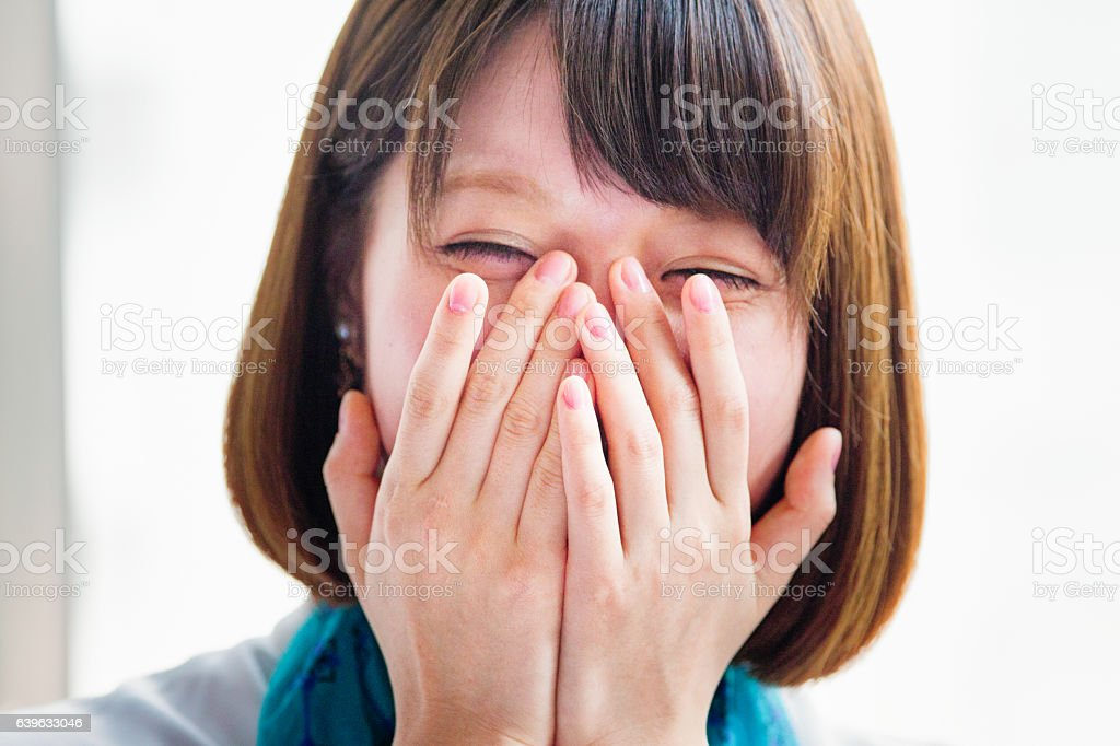 Young Japanese woman hiding her face while laughing. - foto de acervo