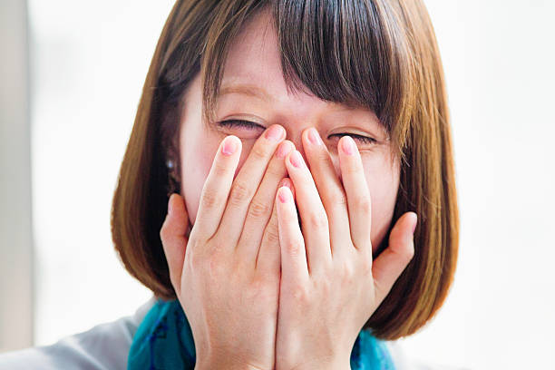 Young Japanese woman hiding her face while laughing. ストックフォト