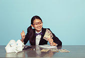 A young Japanese woman dressed as a businesswoman and accountant sits at her desk counting money made from her successful business. Woman makes a happy face at Japanese Yen. Retro styled.