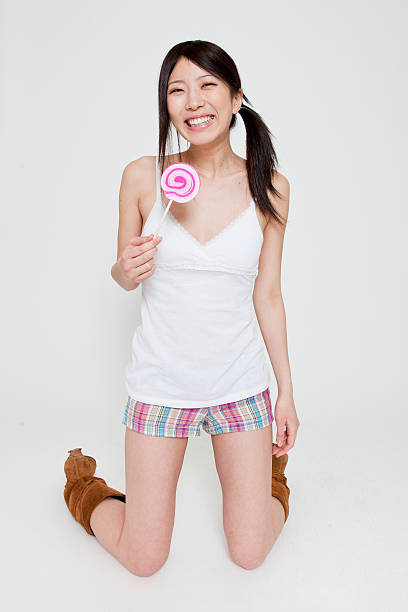 Young Japanese woman kneeling and holding a lollypop stock photo