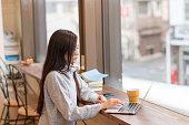 カフェでラップトップを見ている若い日本人女性