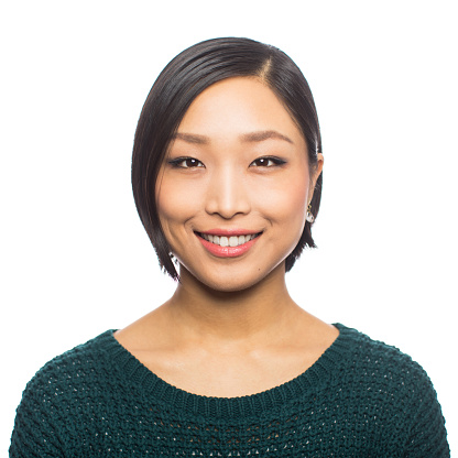 Portrait of young asian woman looking confident against white background. Close-up of Japanese female with short hair looking at camera and smiling.