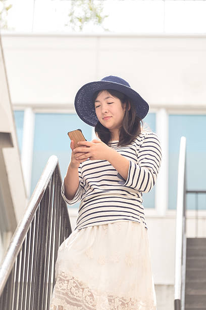 Young Japanese Woman Playing Augmented Reality Game on Mobile Phone ストックフォト