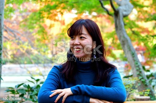 A young Japanese woman is posing in front of bright, colorful autumn foliage in Inokashira Park, Tokyo. Inokashira Park, bordering both Mitaka City and Musashino City of Tokyo Prefecture, is a public park, which was established in 1917, and is open to the public for free access.