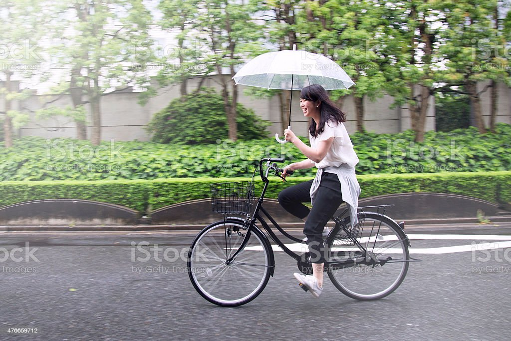 Young Japanese Woman Riding Bicycle on Rainy Day in Tokyo stock photo