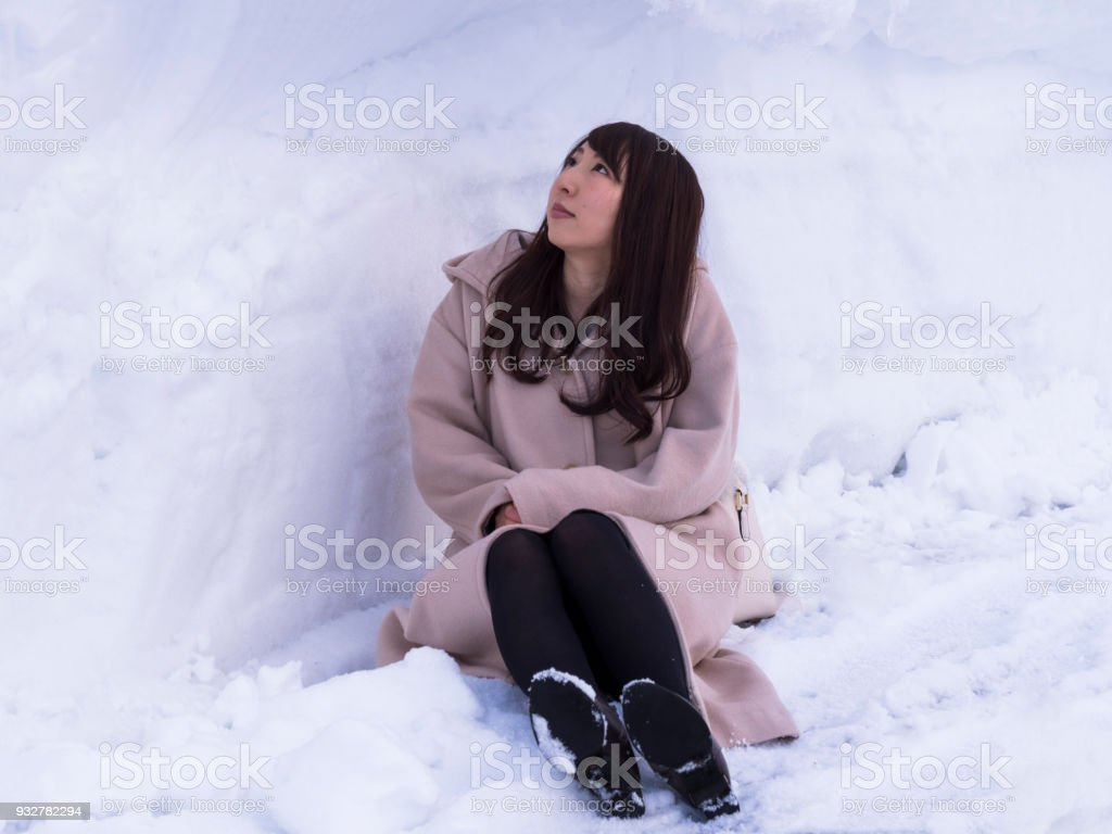 A young Japanese woman sitting in a snow cave. stock photo