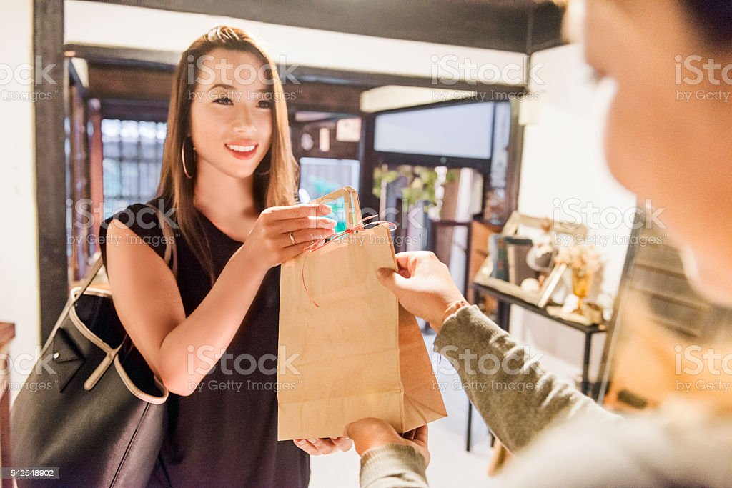 Young Japanese Woman Smiles As She Finishes Shopping Transaction stock photo
