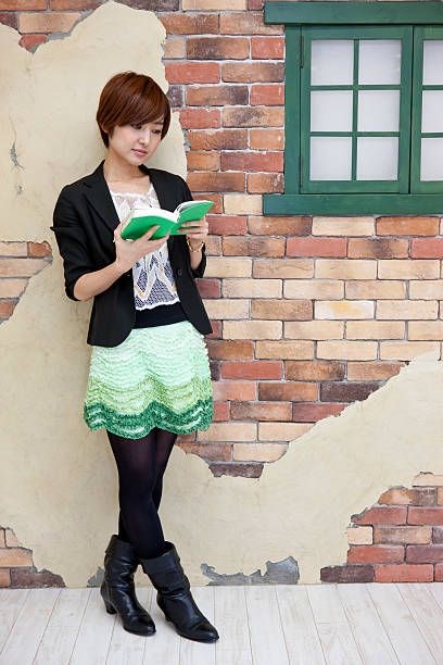 Young Japanese woman stands and reads stock photo
