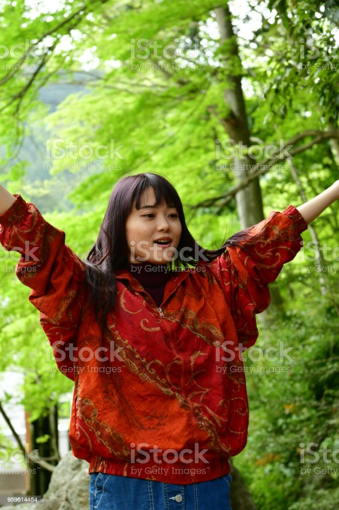 A young Japanese woman is swirling her long hair under fresh green...