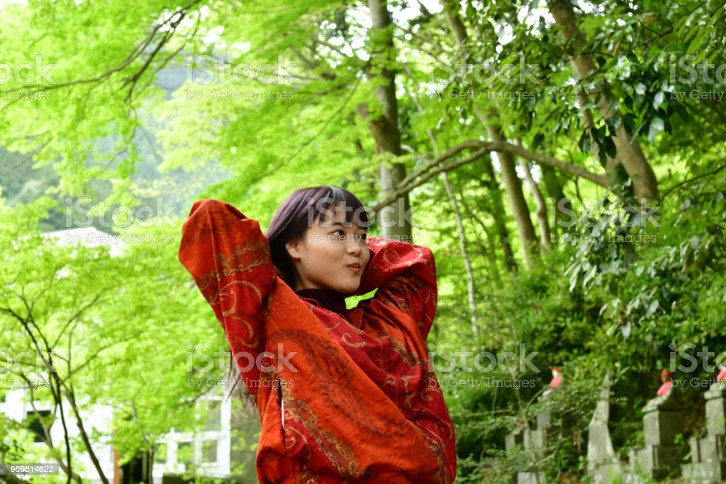 Joven japonesa remolino de su pelo largo con fresco verdor - Foto de stock de 20-24 años libre de derechos