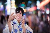 祭りの期間中 Selfie を取って、日本の若い女性