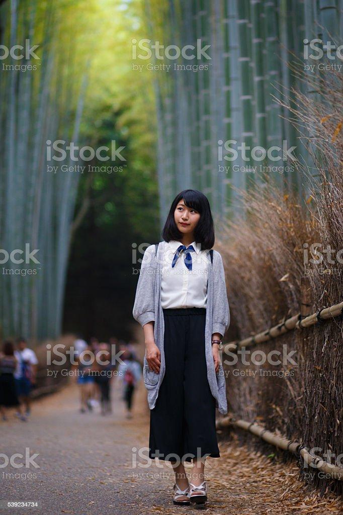 Japonés joven mujer caminando en el bosque de bambú, Kioto foto de stock libre de derechos