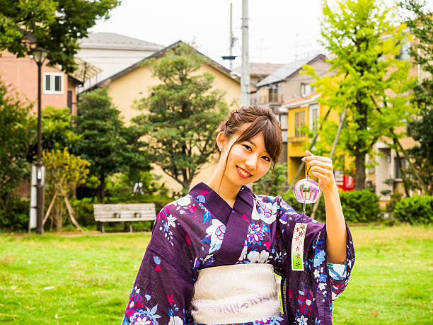 Young Japanese woman walking in the park, with wind chime. stock photo