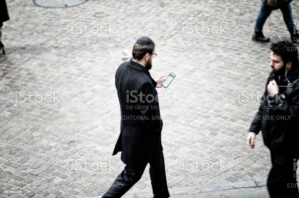 New York City - December 6, 2016: A young Jewish man wearing a traditional yarmulke consults his smartphone as he walks on Wall Street. stock photo