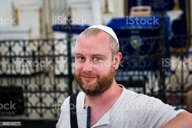 Close up image depicting a young caucasian Jewish adult man in his late 20s or early 30s inside a synagogue. He is looking at the camera and smiling, and he is wearing the traditional Jewish skull cap - otherwise known as a kippah or yarmulke - on his head. The man has a beard and the background of the synagogue is blurred out of focus. Horizontal colour image with copy space.