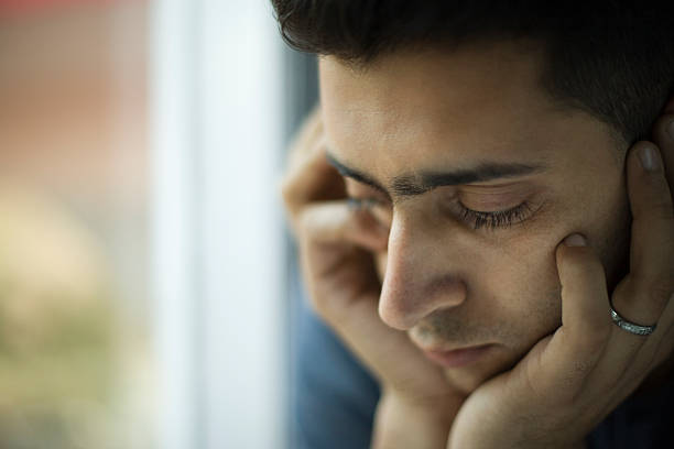 Young jobless man holding his head and thinking near window. stock photo