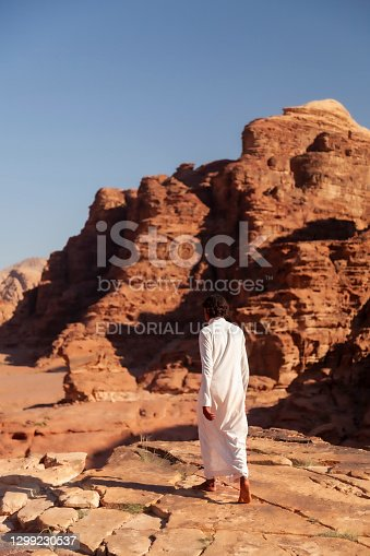 istock A young Jordanian beduin man wearing white Jubba thobe dress is walking bare feet on top of the cliffs 1299230537