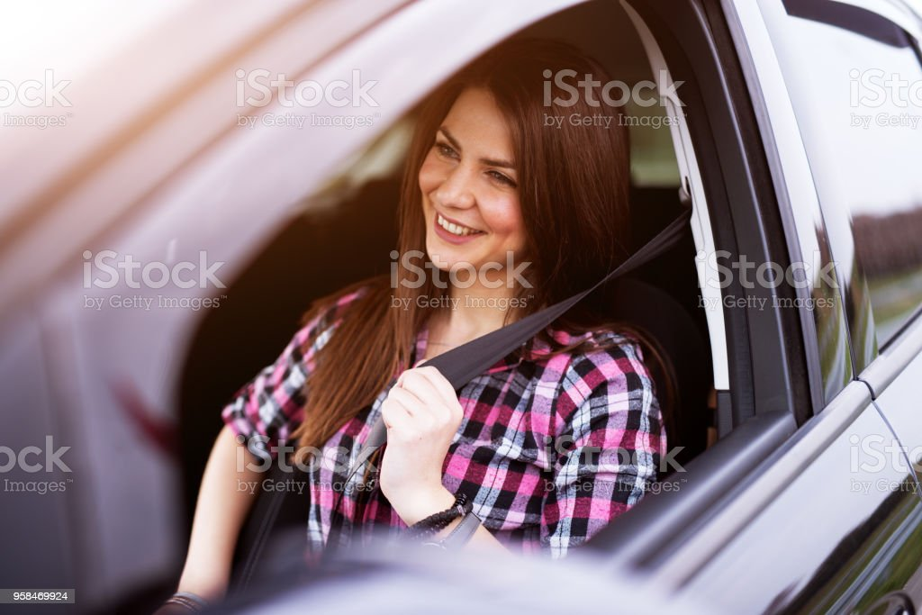 Young joyful beautiful girl is buckling up in a drivers seat of her car. stock photo