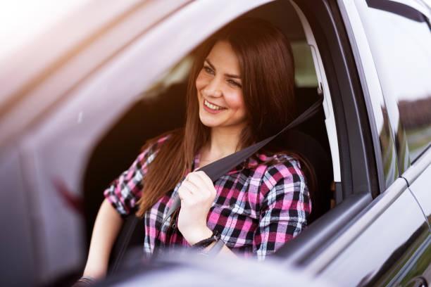 junges fröhliches schönes mädchen ist in einem fahrersitz ihres autos oben knicken. - berufsfahrer stock-fotos und bilder