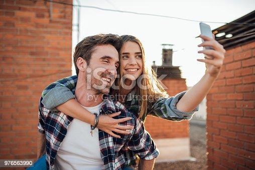 636330566istockphoto Young joyful couple taking a selfie on the roof 976563990