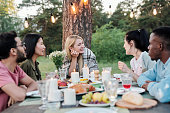 istock Young joyful couples eating and talking by served festive table under pine tree 1271270737