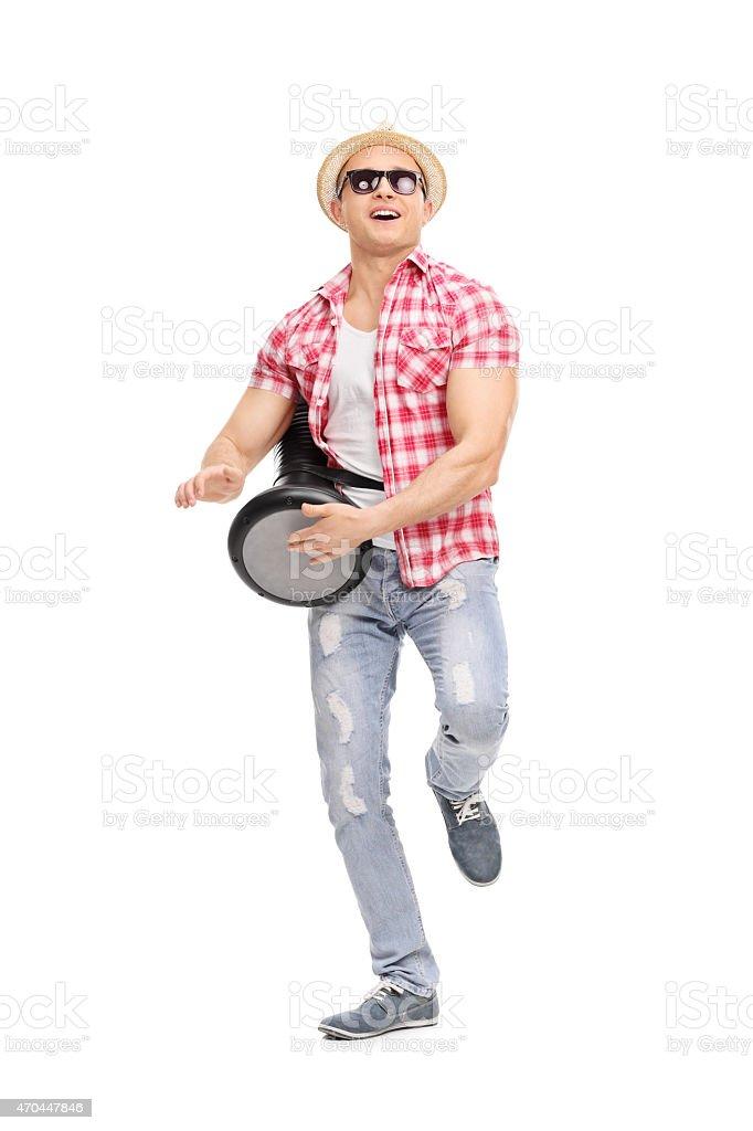Young joyful man playing on a doumbek and dancing stock photo