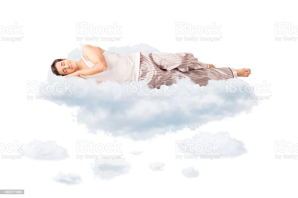 Young joyful man sleeping on a cloud stock photo