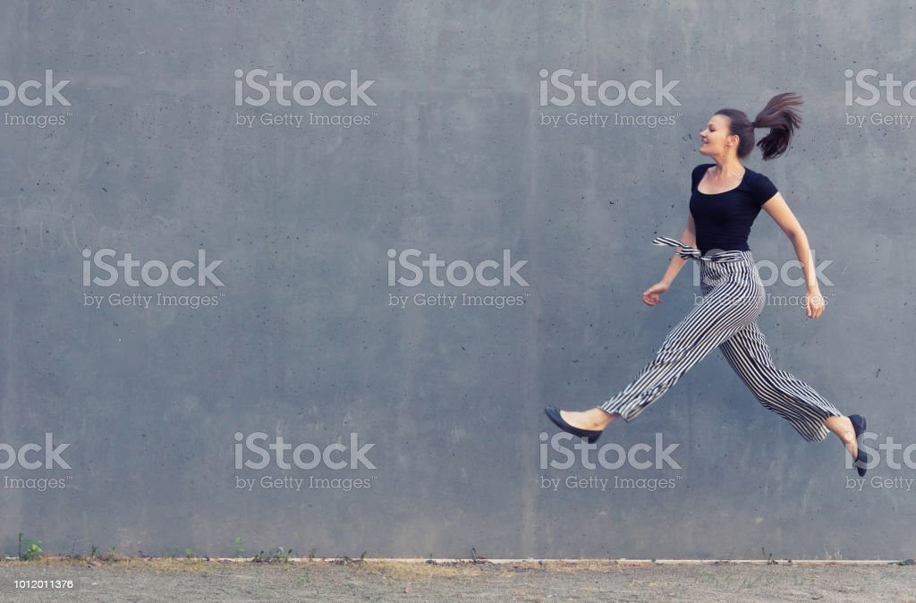 Young jumping woman in front of a concrete wall