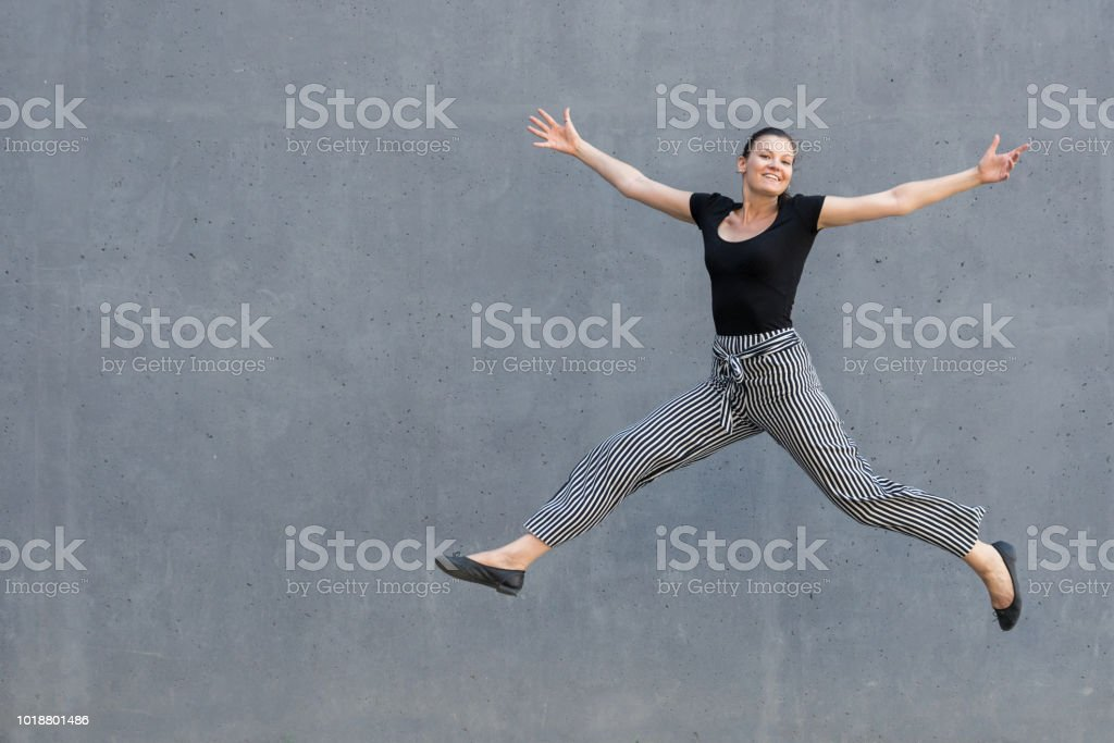 Young jumping woman in front of a grey wall